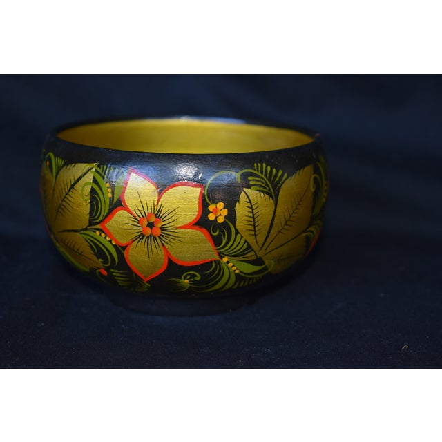 A hand painted Russian lacquered bowl featuring flowers, leaves and cherries executed in a Folk Art style. This is a pre-...