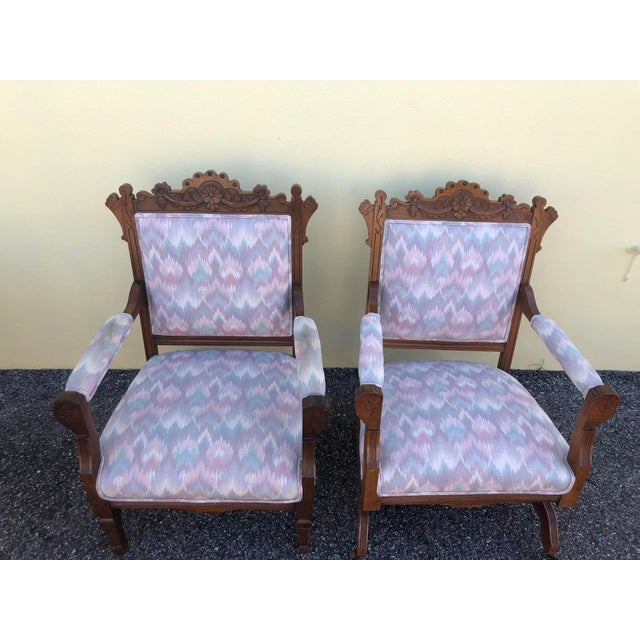 Beautiful Victorian Eastlake platform rocker and arm chairs with carved walnut frame. Both upholstered in a blue, green,...