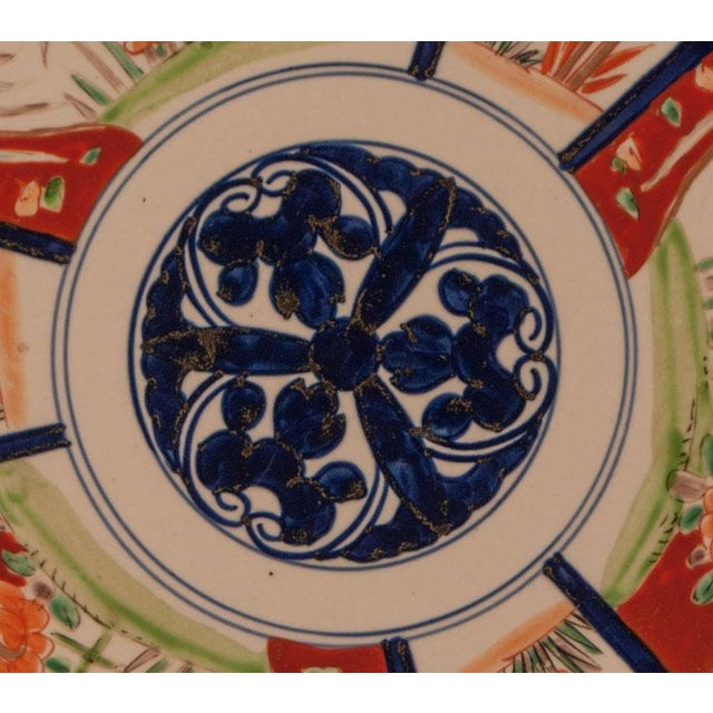 A late 19th century Japanese Imari charger with three flowers in the center.