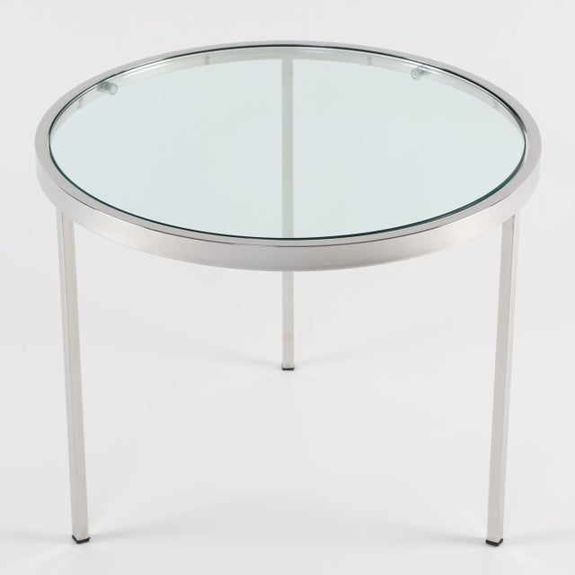 Sleek 1970s Milo Baughman occasional table features a circular chrome frame holding an inset half-inch glass top. Glass is...