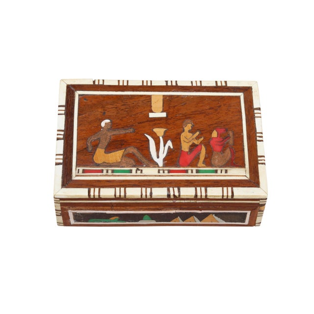 A decorative inlaid trinket box. The case is covered throughout with Egyptian inspired figural marquetry in gold, green...