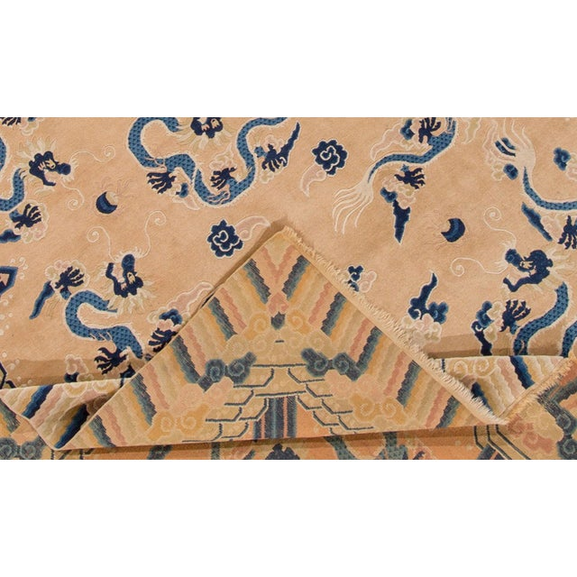 Apadana - Antique Chinese Peking rug. This piece has a light tan/beige field and an all-over dragon motif in blue tones...