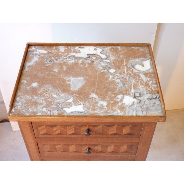 Circa 1900 French marquetry inlaid night table with marble top, dove-tailed drawers, bronze sabots, & bronze accents on...