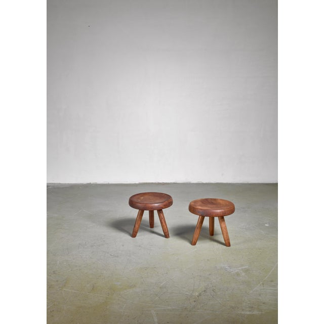 A pair of low tripod stools in stained ash, designed by Charlotte Perriand. The first tripod stool of this type by...