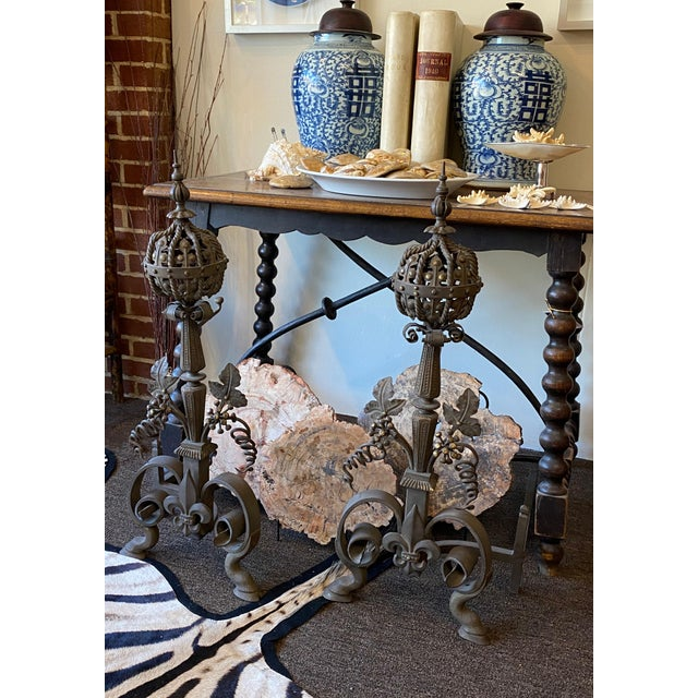 A stately pair of 19th Century French andirons of hand forged wrought iron with floral designs and paw feet.