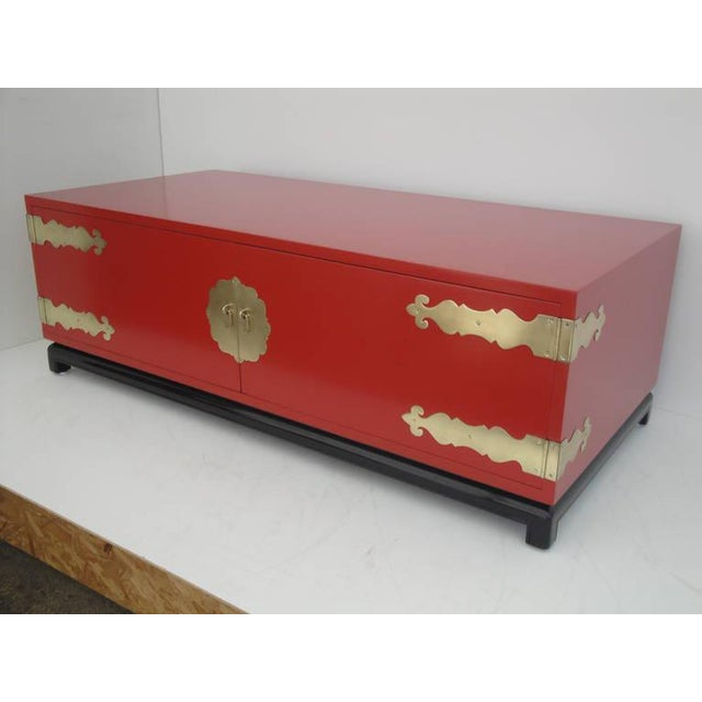 Asian style red lacquered and brass coffee table. Made in the 1960s.