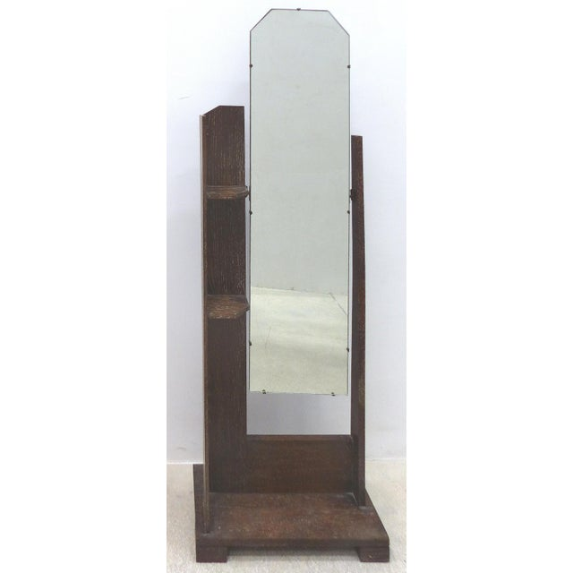 An American cerused oak floor dressing mirror with two small shelves to the left side. The full length mirror has angled...