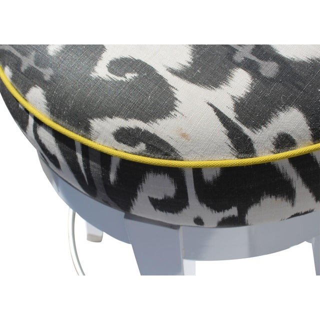 Set of three custom white lacquer swivel dining stools, upholstered in Christopher Farr white, black, and gray ikat fabric...