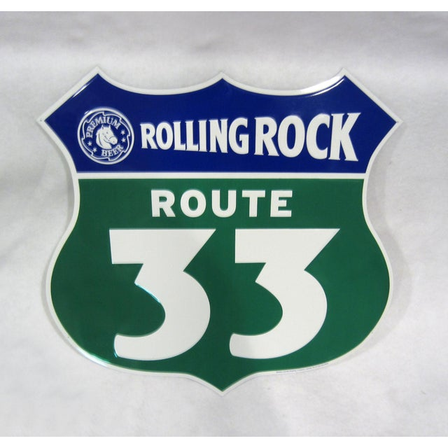 An embossed metal shield-shaped sign advertising Rolling Rock Premium Beer, in excellent condition. Marked ©2002 Latrobe...