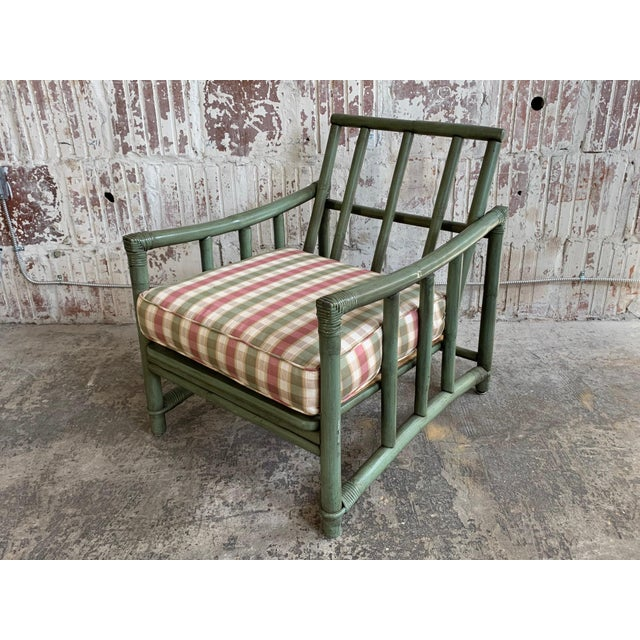 Mid-century rattan bamboo arm chair by Ficks Reed features a gorgeous green frame and a perfect amount of patina from age....