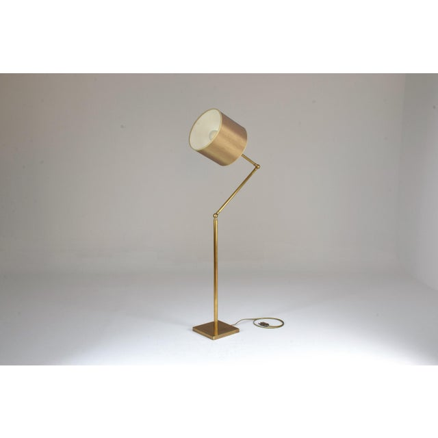 A vintage articulating newly polished brass floor lamp designed with a stylish arm that adjusts twice mid-arm. The base is...