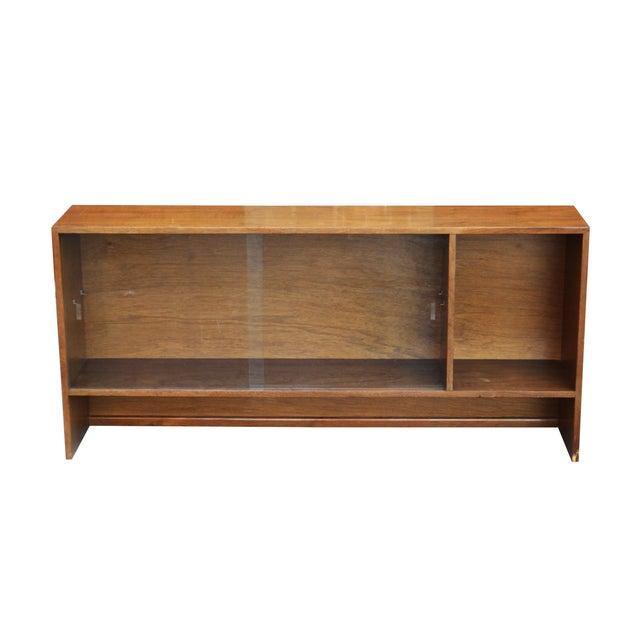 Walnut bookshelf with sliding glass doors. It has shelf pin holes for a potential shelf, though no shelf is included...