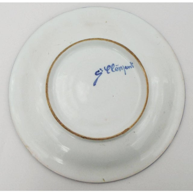 A small French faience platter with a floral pattern inspired by the Renaissance, signed Saint Clement, circa 1900.