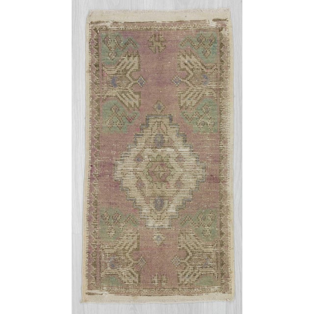 Handknotted vintage mini rug from Oushak region of Turkey. In good condition.