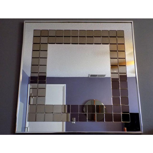 A unique find in this 1970's vintage wall mirror by Hal Bienenfeld, studio stamp on rear. 80 individual smoked mirror...