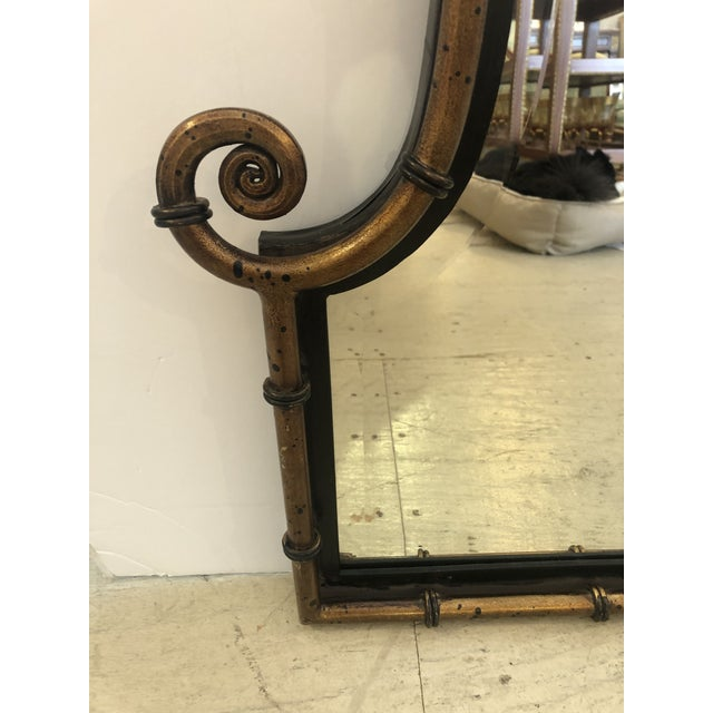 Stylish pagoda style mirror having antiqued bronze color on faux bamboo frame with black details and curlicues near the...