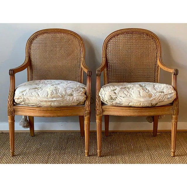 A pair of early 19th century French fauteuils in the Louis XVI style with cane backs and fabric seats on tapering fluted...