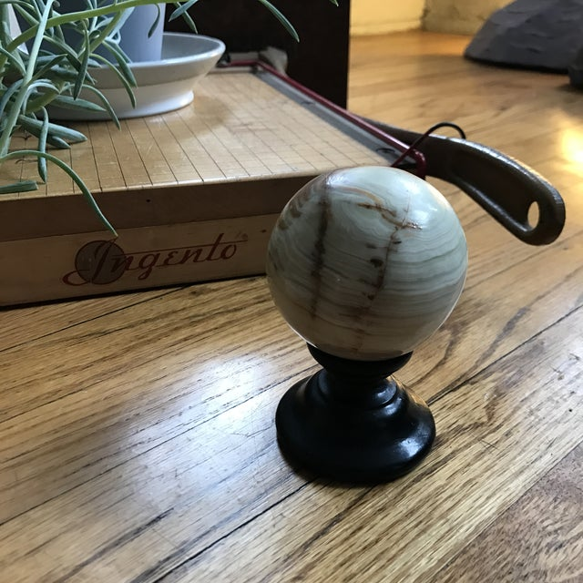 Travertine is a banded, compact variety of limestone and onyx formed along streams and waterfalls. This sphere has a ebony...