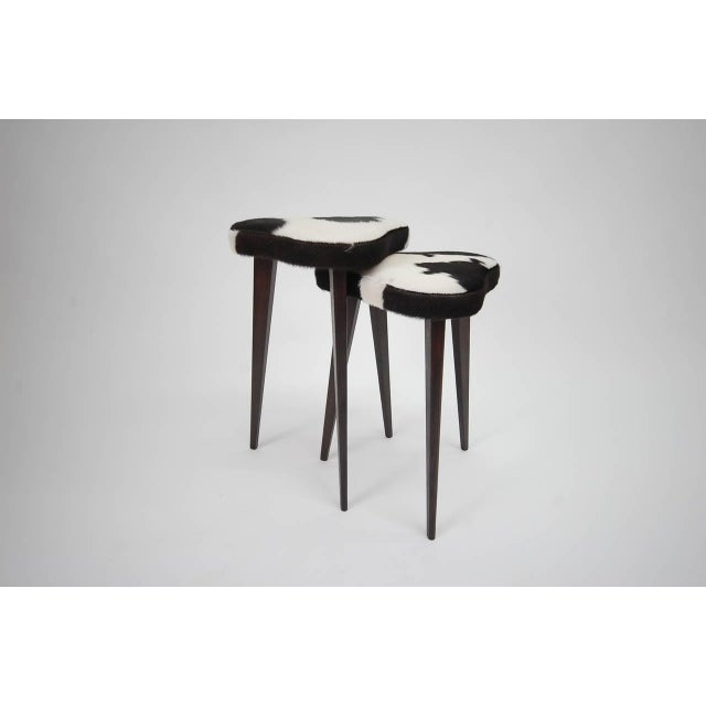 Pair of small nesting stools from France, newly upholstered in cowhide. The oak legs have been refinished to a dark brown....