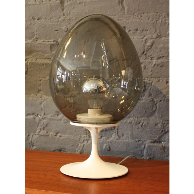 This stunning table lamp features a white tulip base and smoked glass egg-shaped shade. Designed in 1965 by Bill Curry as...
