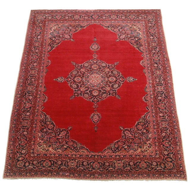 Offered is a Persian Kashan rug. This gorgeous piece features tones of red, black, and tan throughout the hand knotted...