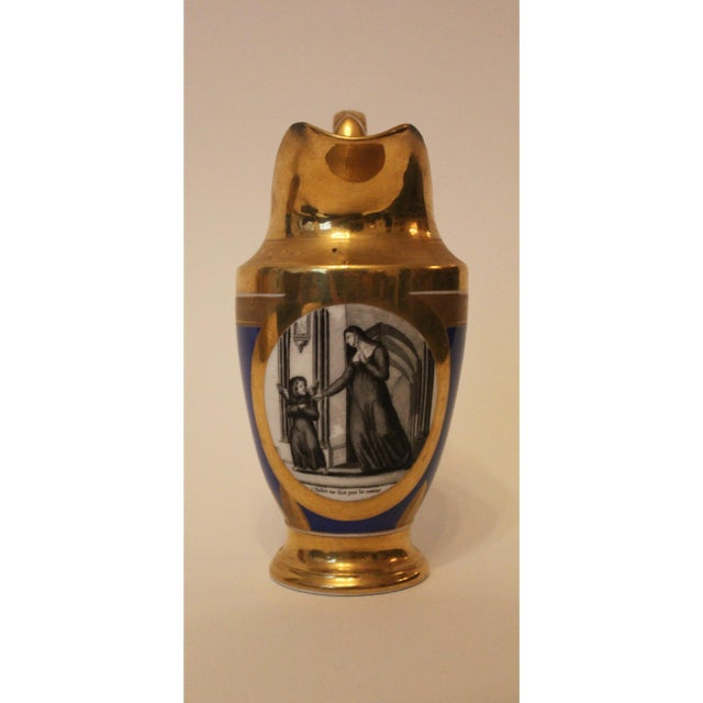 Stunning gold and cobalt blue ewer has a subtle pattern of leaves and scalloped edges. The charming grisaille image...