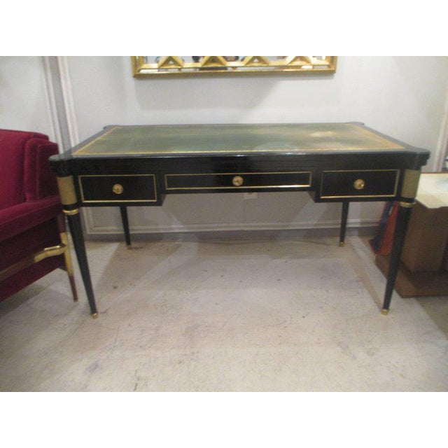 French directoire-style bronze-mounted and ebonized bureau plat desk with three drawers on tapered legs ending in brass...