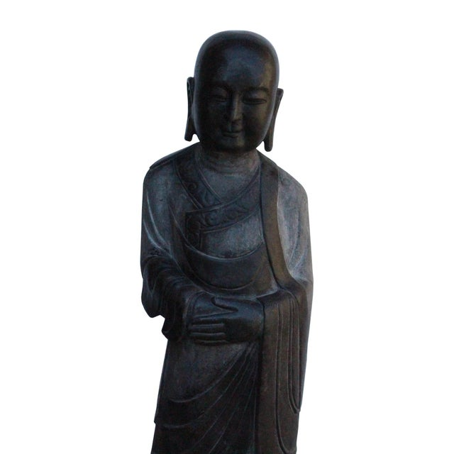 This is a gray black color stone statue of oriental Zen Monk Lohon is standing position with prayer hand posture. It is...