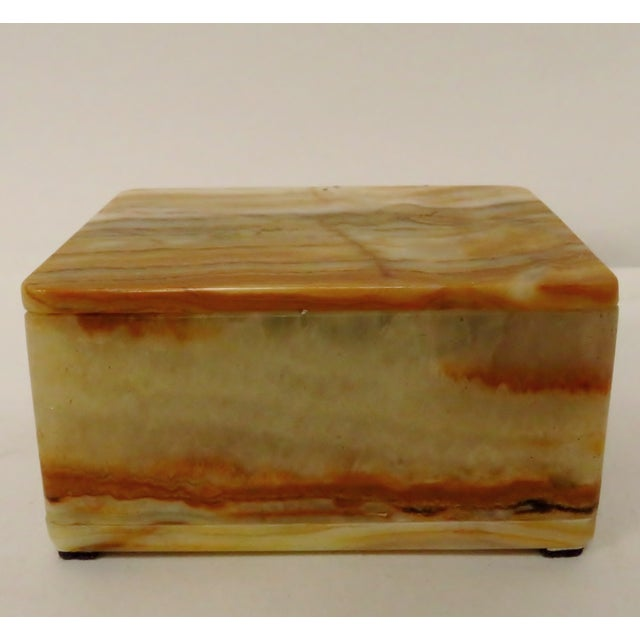 A small carved and polished onyx stone box with hinged lid in shades of caramel, gold and cream. There is a beautiful...