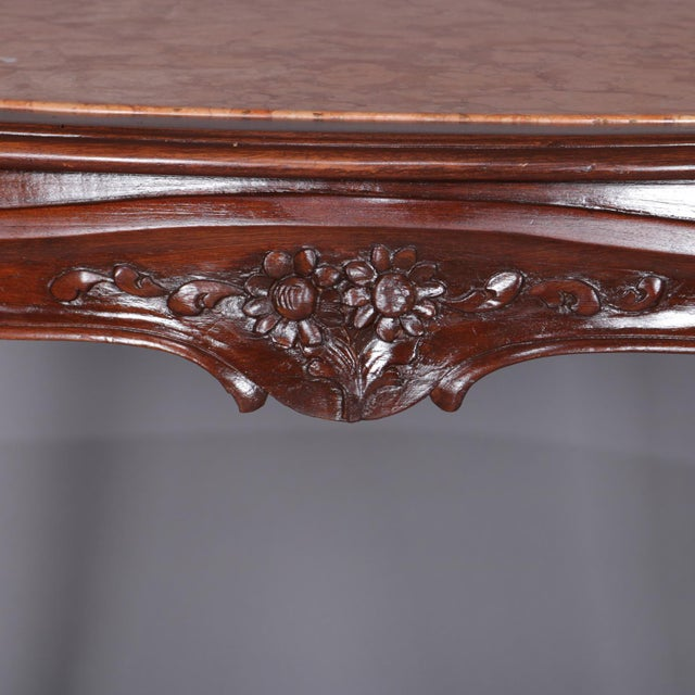 An antique French Louis XV style center table features inset marble top surmounting walnut frame with scalloped apron...