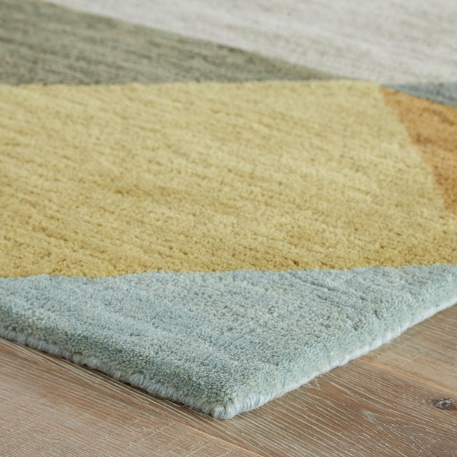 This hand-tufted area rug charms on-trend spaces with mid-century modern style and plush texture. Gold, teal, blue, and...
