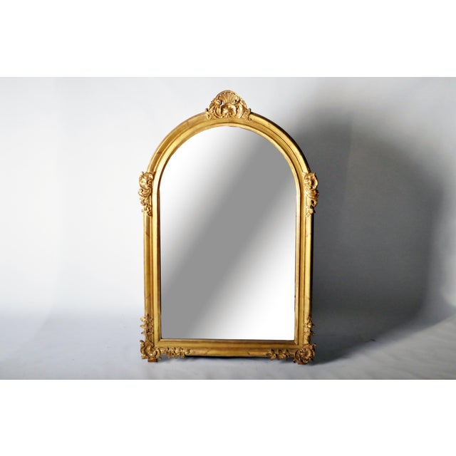 The large arched rectangular mirror plate is framed by intricately carved Rococo motifs. Swirling C-scrolls flank the...