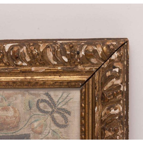 Framed needlework picture of man and a bird with floral border and gold distressed frame.