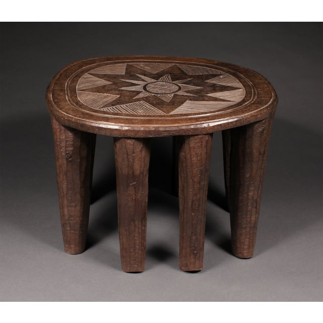 Eight bold, tapered legs support this sturdy, carved wood stool crafted by the Nupe Tribe in Nigeria. The top features a...