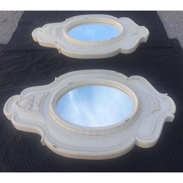 Pair of French oval wall mirrors with. Made of heavy wood. No maker's mark. Hanging hardware included