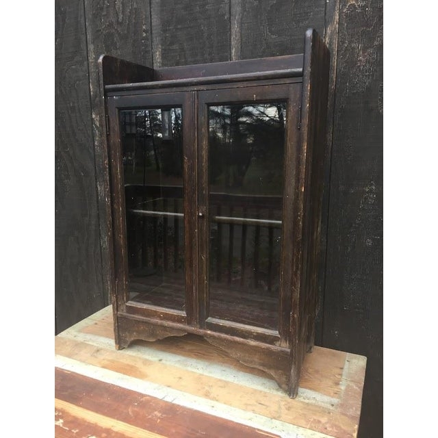 This distressed wooden bookcase or curio cabinet . The cabinet is sturdy and does not feel frail or wobbly. The glass...