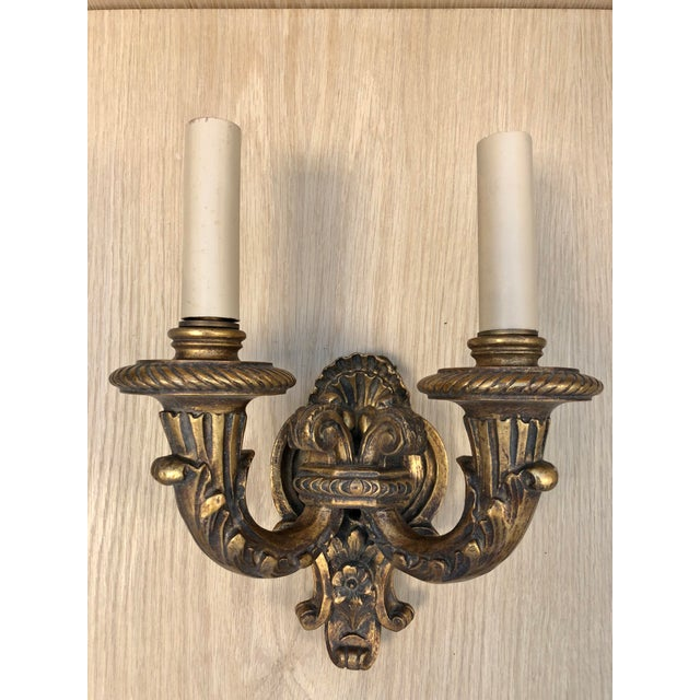 Pair of Traditional Wood Carved 1920's Vintage Two Arms Antique Gilded Wall Sconces. These wall sconces came out of an old...