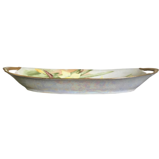 This beautiful floral serving dish is made of iridescent porcelain with a gilt edge and handles and features yellow...