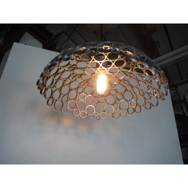 Inspired by the work of Queens's lamp designer Louis comfort Tiffany this pendant associates aluminum and light for a...