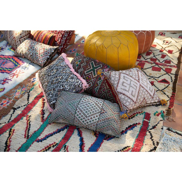 This one-of-a-kind hand-woven vintage Berber pillow is made by Berber women living in the Middle Atlas Mountain range of...