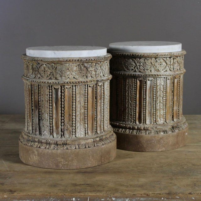 A pair of intricately carved 18th century English pine pedestal bases with traces of original gesso and original inset...