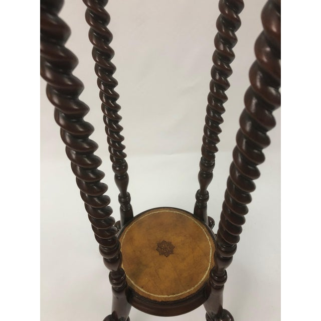 A handsome tall mahogany stand having barley twist structure and tooled leather on both circular surfaces with central...
