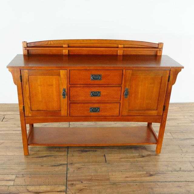 A Mission-style Bassett Furniture sideboard, wood construction with oak and ash wood veneers. Its cabinet is comprised of...