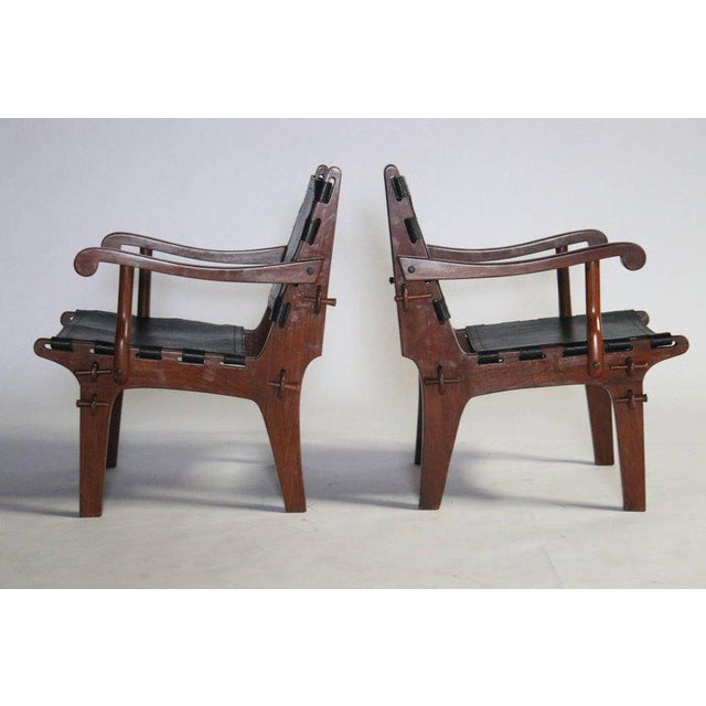 Pair of Brazilian modern rosewood and black leather sling armchairs with corset straps by Angel Pazmino. These chairs were...