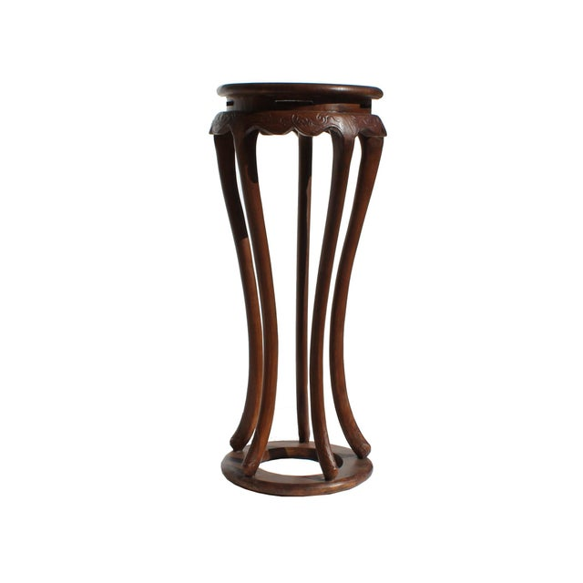 This is a handmade simple tall plant stand, pedestal table with a brown stain on the surface showing natural wood patina....