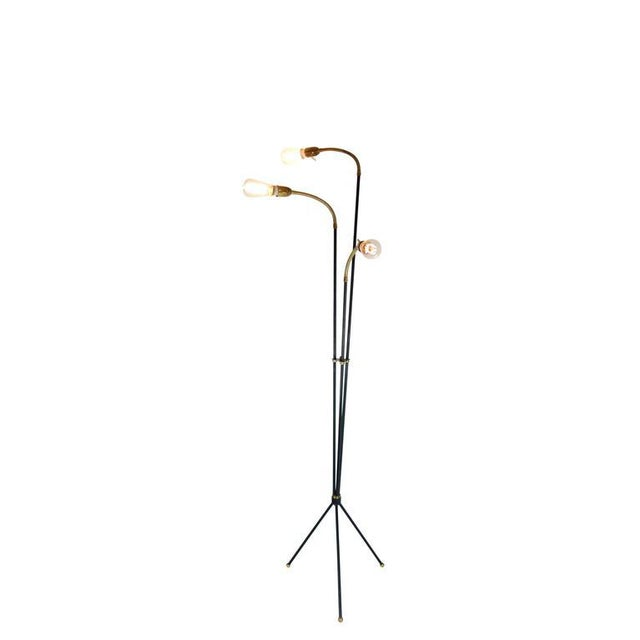 This is a painted steel Mid-century tripod floor lamp with brass details and three articulating arms from Denmark, circa...