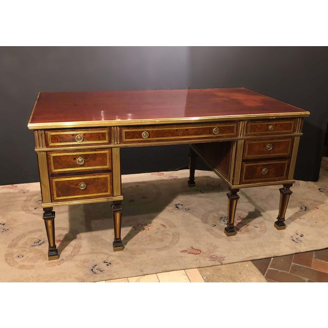 A large Russian neoclassic mahogany desk with brass trim and moldings, on square tapered and fluted legs.