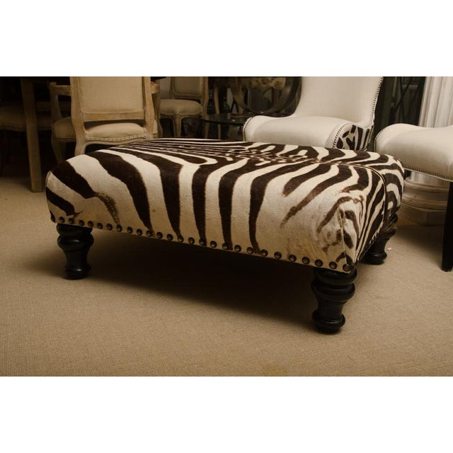 Attractive ottoman covered in a zebra skin. The zebra skin is in excellent condition