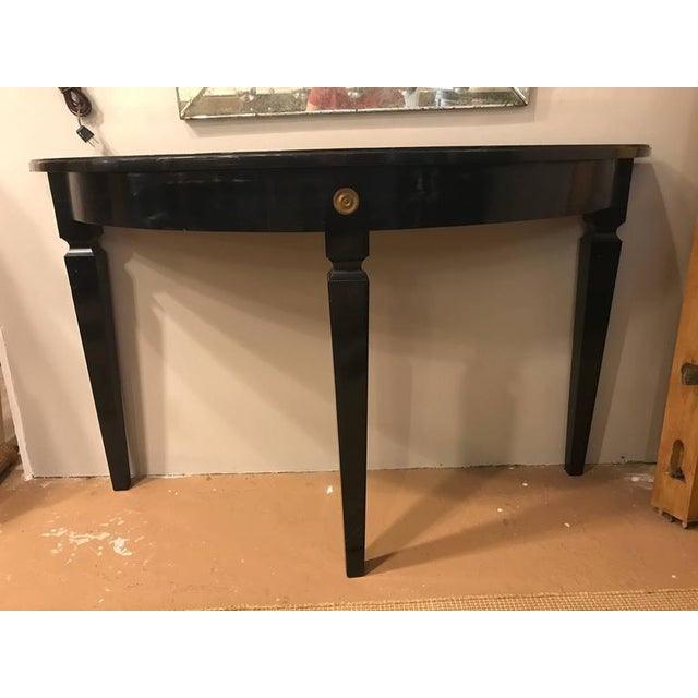 Églomiséd demilune console table by Maison Jansen. The ebonized base having long sleek tapering legs terminating in bronze...
