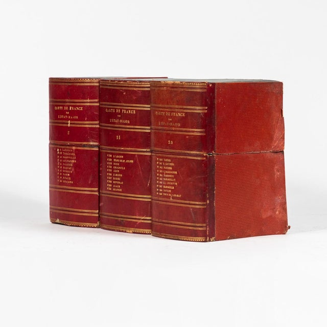 A collection of 22 red book boxes with blue interior. Originating in England, circa 1900.